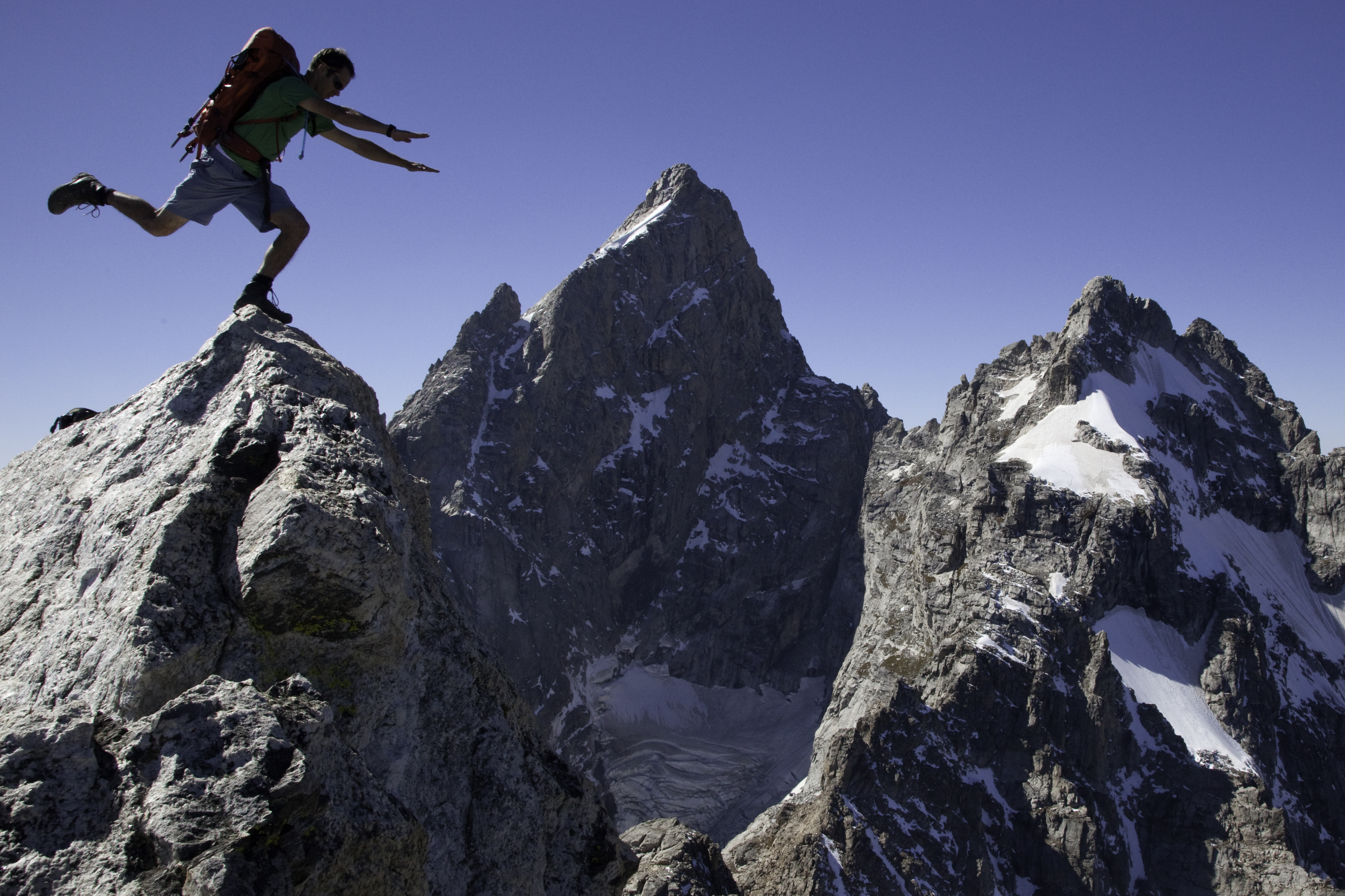 Climber on the summit of Teewinot with the Grand Teton and Mount Winster in the background.