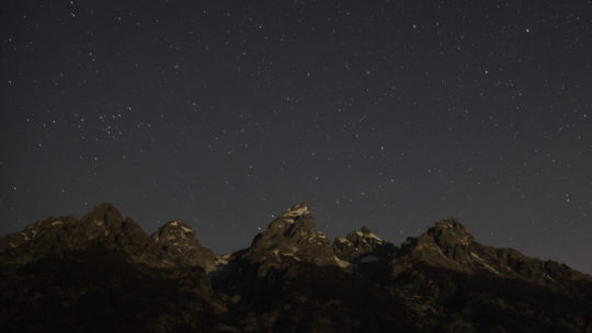 Stars and Constellations Appear In The Night Sky Above The Grand Teton Range