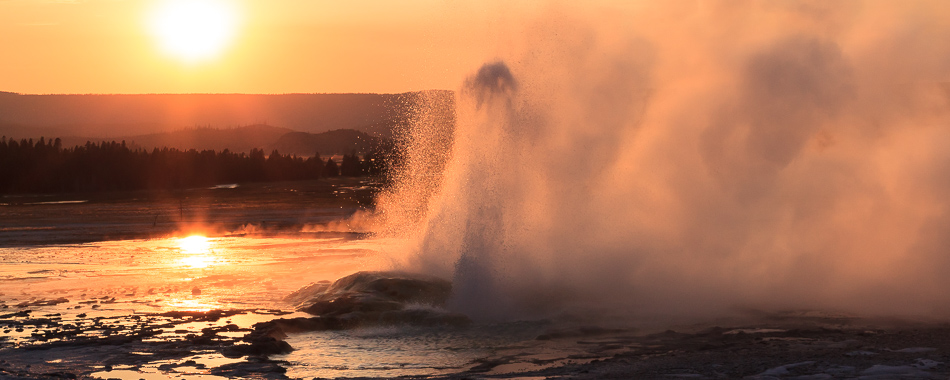 Geyser erupting at sunset at the Lower Geyser Basin in Yellowstone National Park.