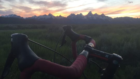 A Bicyclist Pauses In Front Of The Grand Teton Range During A Commute Home From Work