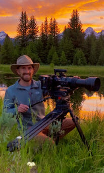 Brandon Navratil Works A Camera In The Field With Mountains And Sunset In The Background