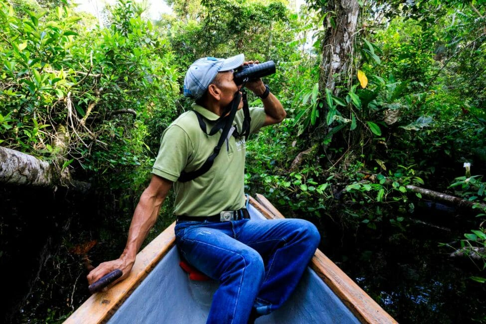 man using binoculars in canoe in the amazon