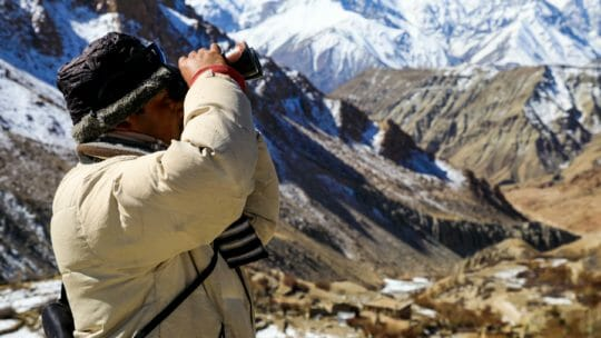 man using binoculars to view the himalayas