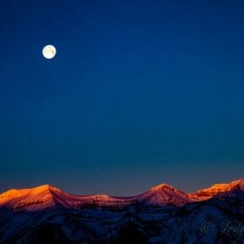 A Full Moon Hangs Over The Snow Covered Teton Mountains In Jackson Hole, Wyoming.
