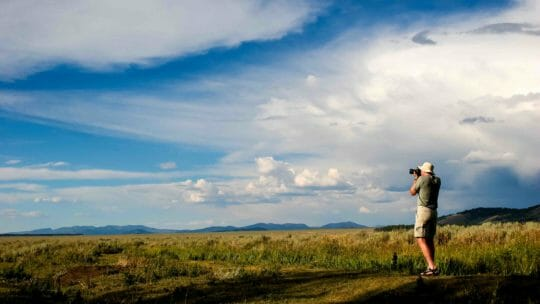 man photographing field in Grand Teton National Park.