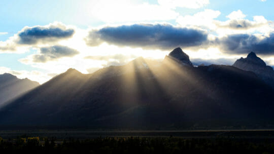 Sun Rays Break Over The Peaks Of The Teton Mountain Range In Grand Teton National Park