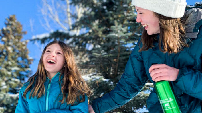 two girls laughing in the snow holding a water bottle