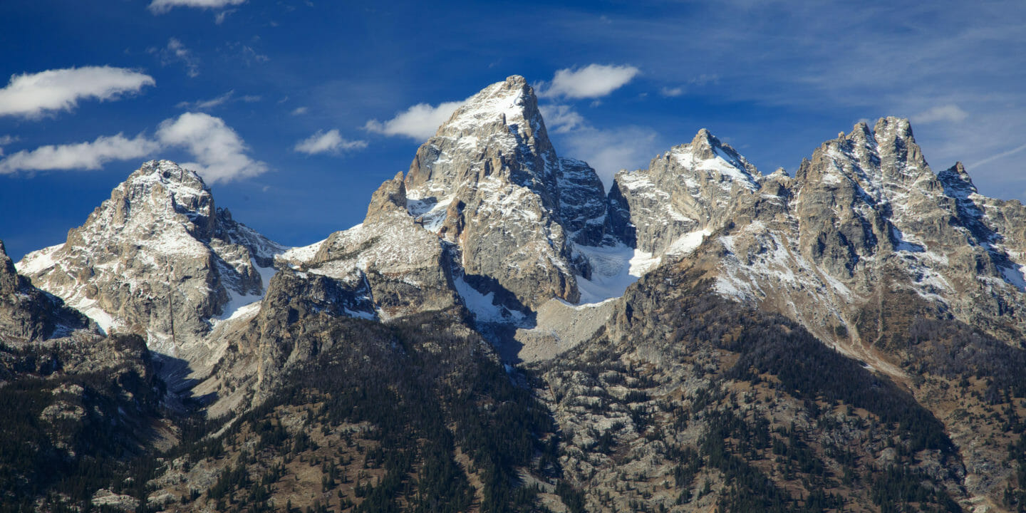 The Grand Teton Range Is An Impressive Skyline Against A Bright Blue Sky