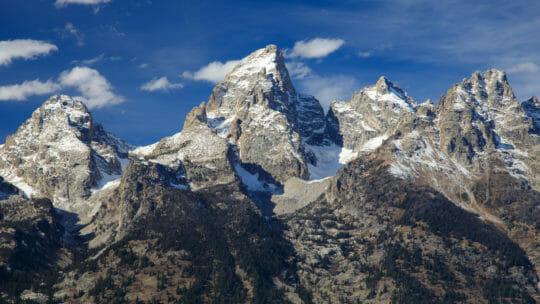 The Grand Teton Range Is An Impressive Skyline Against A Bright Blue Sky