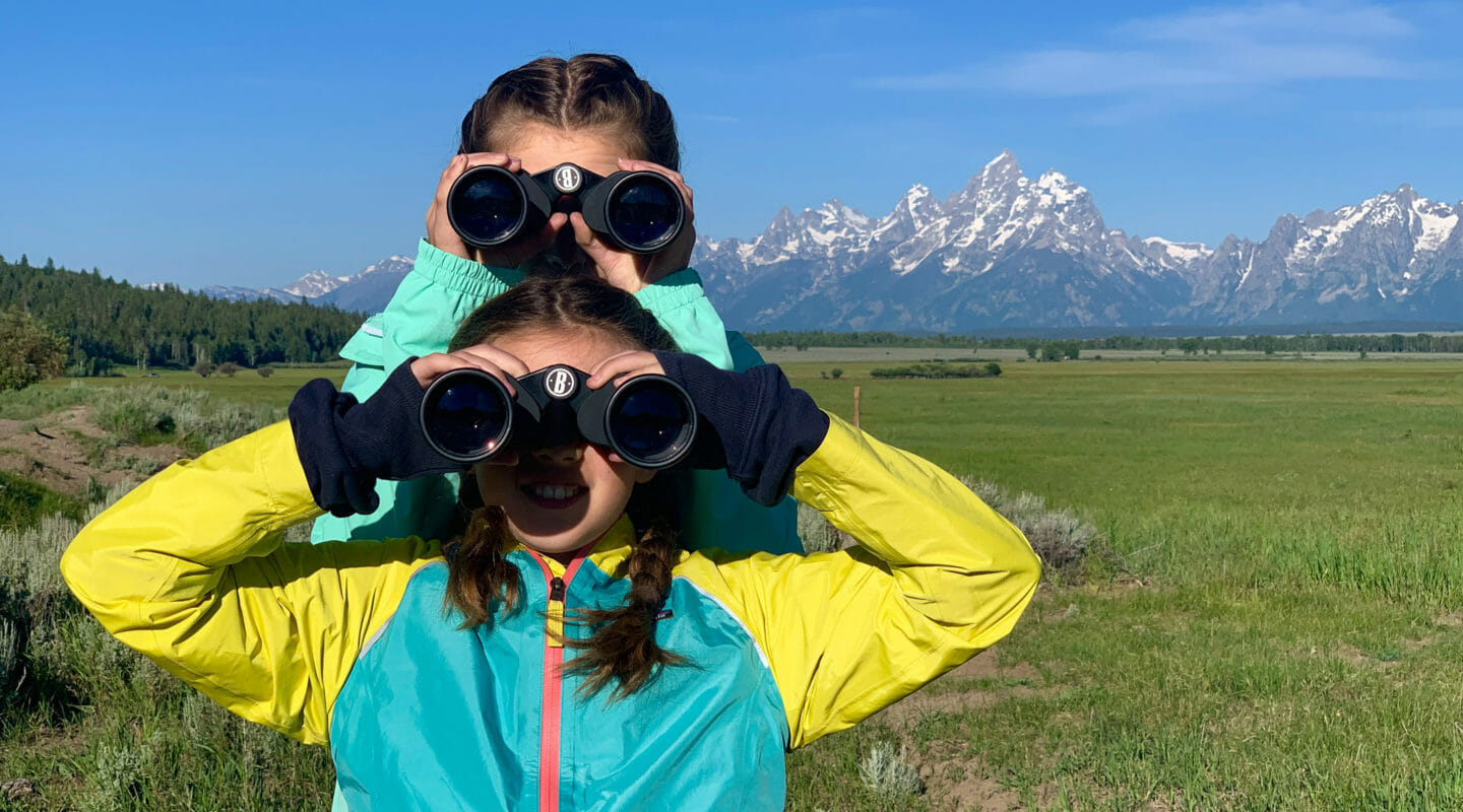 Two Girls Look For Wildlife Through Binoculars While On Safari In Grand Teton National Park