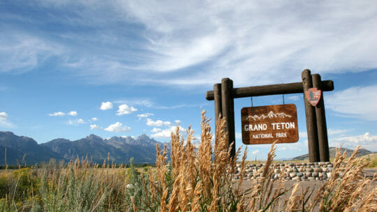 A Wooden Sign Marks The Southern Entrance To Grand Teton National Park
