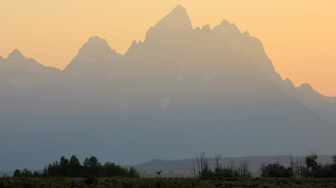 The Iconic Peaks Of The Teton Range Are Silhouetted Against A Warmly Lit Sunset In Grand Teton National Park